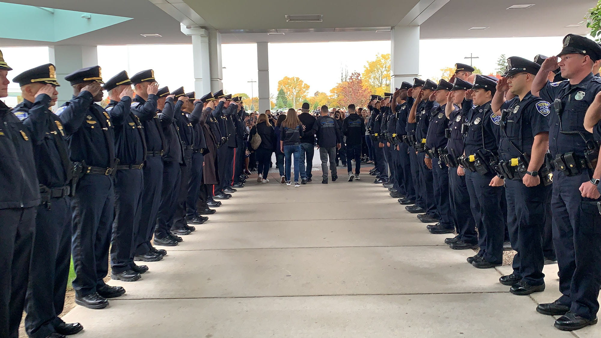 Police officers saluting Officer Denny Wright