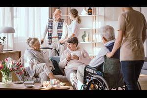 Elderly men and women talking in the common room in nursing home
